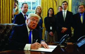 U.S. President Donald Trump looks up while signing an executive order to advance construction of the Keystone XL pipeline at the White House in Washington January 24, 2017.  REUTERS/Kevin Lamarque      TPX IMAGES OF THE DAY