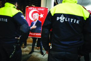 epa05843195 A protester holds a placard with a picture of Turkish President Erdogan as hundreds of demonstrators protest outside the Turkish consulate in Rotterdam, the Netherlands, 11 March 2017. The protesters were demanding to see the Turkish Family Minister Fatma Betul Sayan Kaya who was barred by police from entering the Turkish consulate in Rotterdam. Earlier the day, Dutch government denied landing rights to Turkish Foreign Minister Cavusoglu who planned a speech at the consul's residence in Rotterdam.  EPA/Bas Czerwinski